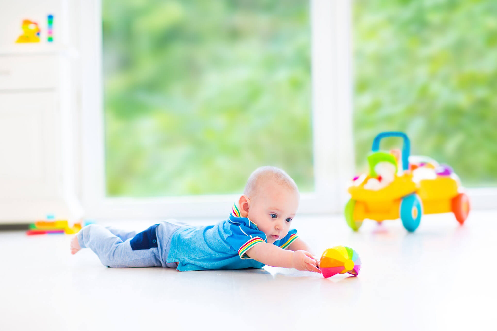 A baby boy lies on his stomach on the floor and plays with a toy